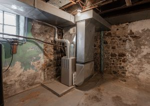 Prevent your furnace from leaking water with regular maintenance, like this furnace in an older basement that needs to be repaired before winter.