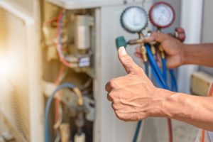 technician performing HVAC repairs and giving thumbs up
