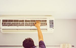 Repairman fixing air conditioning system. We have a list of common air conditioning problems and what to do about them.