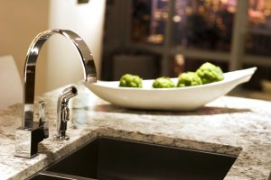 A kitchen sink and marble countertop.